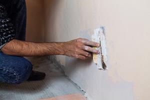 construction worker repairing drywall